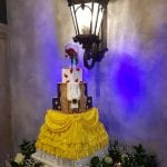 A beauty and the beast inspired wedding cake, half projection and half sugar crafted the bottom was ruffles next two tiers were the dress and then the beasts jacket.