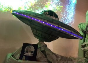 A 3 foot wide gravity defying UFO made for cake international on tour, The cake side of the moon exhibit . This ufo is covered in modelling chocolate then painted and airbrushed with a flashing light strip along the outside .