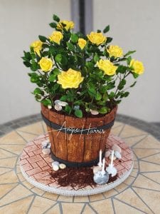 Rose Bush Cake, the pot is made up of vanillla sponge buttercream and jam hand carved, with the roses and leaves are all hand made individually in white florist paste then all airbrushed and dusted and put together with about 18 leaves to 1 rose stem